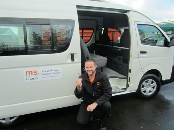 Don kneeling next to mobility van holding key