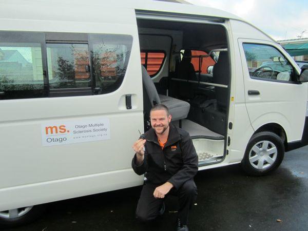 Don kneeling next to mobility van holding key